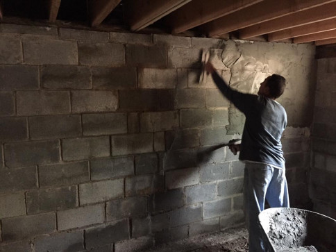 During - Workers Plastering Basement Wall